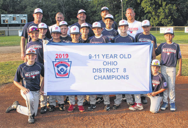 2019 DISTRICT 8 CHAMPION WASHINGTON C.H. 11-YEAR-OLD ALL-STARS — The team gathers on the mound with their championship banner after defeating Enon 15-0 Tuesday, July 23, 2019. (kneeling, at left); Cooper Enochs; (kneeling, at right); Aden Osborne; (first row, l-r); Kaden Bryant, Jameson Hyer, Luke Armstrong, Cameron Morton, Austin Brown, Kyler Vernier, Lucas King, Noah Haithcock, Cooper Robertson, Andrew Young, Javin Baker; (back, l-r); manager Aaron Robertson and coaches Todd Brown, Jeremy Hyer, Steve Haithcock and Josh Morton.