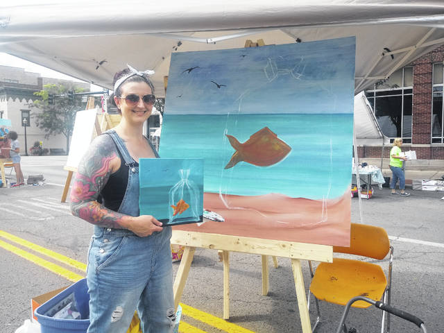 "An employee of True Blue Tattoo, Amanda Foy, brought along a small-scale version of her project and paused during painting to answer questions from those watching her work. She laughed when asked the difference between tattoos and painting and said, ""Canvas is a lot nicer than skin."""