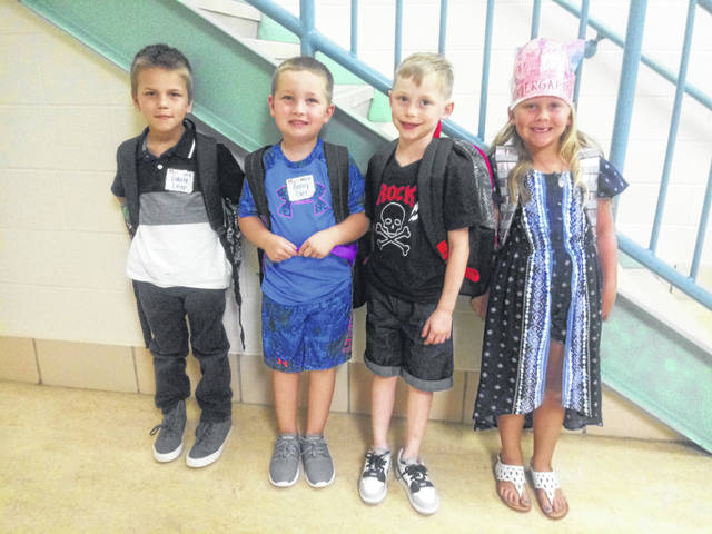 "Half of the kindergarten class at WCHCS Cherry Hill Primary attended their first day on Tuesday. The other half will begin school on Wednesday. Kindergartners (L-R) Dakota Estep, Benny Carr, Ian Huff and Carleigh Justice were waiting with their teachers and fellow classmates at the end of their school day for their bus to arrive. Cherry Hill Principal Craig Maddux explained the first and second graders began school on Monday but they stagger the days for kindergartners to begin school. According to Maddux, the first and second grade students set great examples for the kindergartners. He said, ""I have been so proud of them. They have settled in. They have done such a nice job following the rules and making good choices. I think we're off to a wonderful school year."""