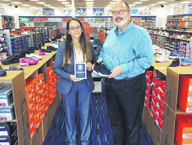 The City of Washington C.H. recently presented Shoe Show, located at 1359 Leesburg Ave., a new business plaque. Pictured are the store manager, Monica Akers, and City Manager Joe Denen. Shoe Show offers lots of name-brand shoes.