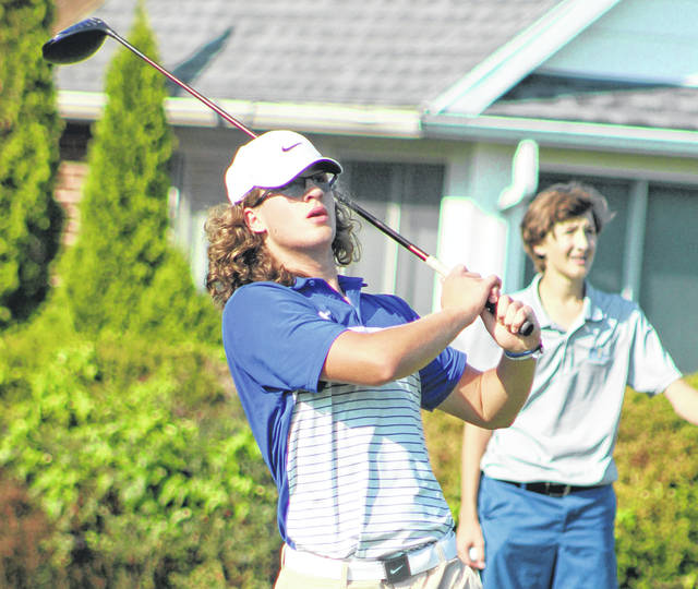 Washington senior Brock Morris watches the flight of his tee shot during a non-conference tri-match with Vinton County and Grandview Heights Monday, Aug. 19, 2019 at The Greens course. Also pictured is Brendan Cleary of Grandview.