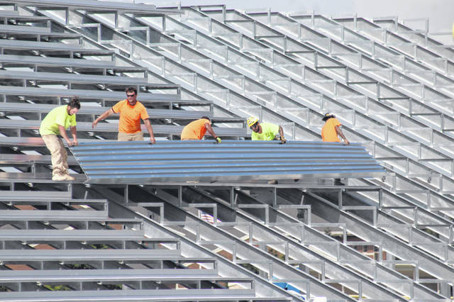 Crews worked Wednesday to continue building the bleacher structure on the Miami Trace Local Schools campus that will serve as the home side of the football stadium for a portion of the season by placing seats, railings and more. Business Manager Bill Franke said he expects the actual home side project to be completed by the end of September or sooner if weather cooperates and crews keep up the effort.
