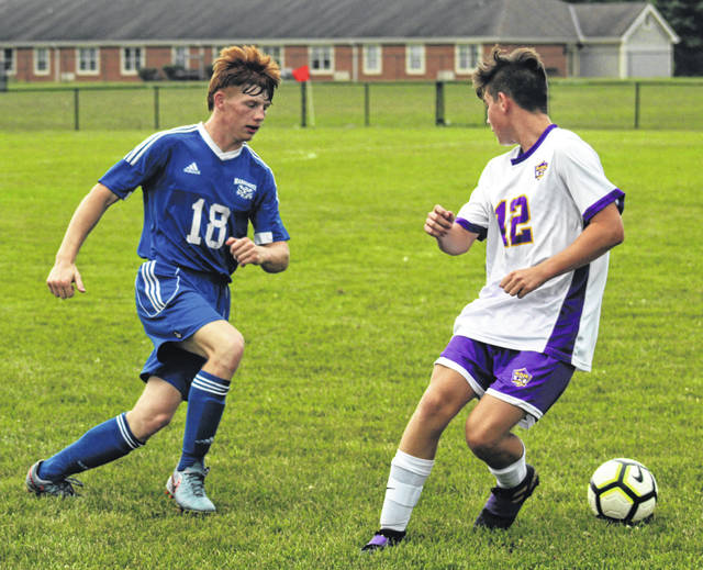 Washington senior James Baughn (left) kicks the ball behind a player from McClain during a Frontier Athletic Conference-opening match Tuesday, Aug. 27, 2019 at Washington High School. McClain won the game, 16-0. The Blue Lions will host FAC opponent Hillsboro Thursday at 5 p.m.