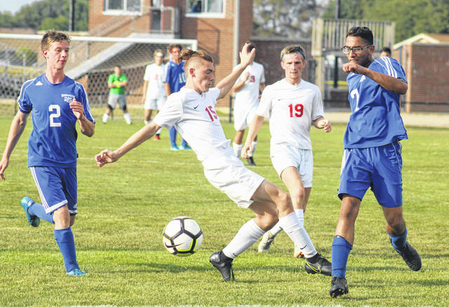 Shlok Shah (7) advances the ball for Washington during a Frontier Athletic Conference match against Jackson Thursday, Sept. 12, 2019 at Washington High School. Also pictured for the Blue Lions is Preston Hines (2). Jackson won the match, 15-0. Washington will be back in action Tuesday at Miami Trace at 5 p.m.