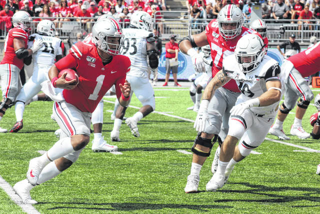 Ohio State sophomore quarterback Justin Fields (1) carries during the game against the University of Cincinnati Bearcats Saturday, Sept. 7, 2019 at Ohio Stadium. Also pictured for Ohio State (at right) is fifth-year senior offensive lineman Branden Bowen. Fields completed 20 of 25 passes for 224 yards and two touchdowns (with no interceptions). He carried the ball nine times for 42 yards and two touchdowns (7 and 4 yards).