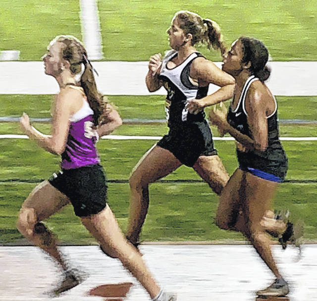 Miami Trace's Kylie Pettit (middle) competes in a night race at Dublin Coffman High School Saturday, Sept. 21, 2019.