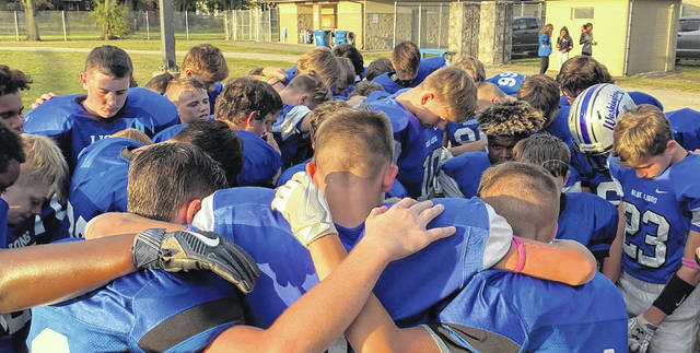 Washington Blue Lion seventh and eighth grade football players have a prayer for the aunt of two of the players, Tomi Kay Shaw, who is hospitalized in Cleveland following a near-drowning accident in Florida. The prayer took place between games against Miami Trace at Gardner Park Tuesday, Sept. 24, 2019.