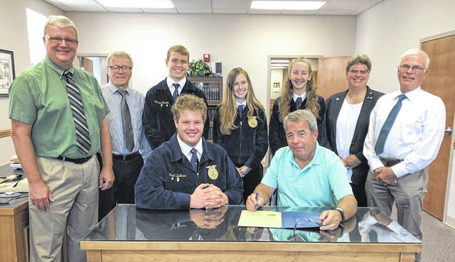 On Monday, the Fayette County Commissioners signed a proclamation for Miami Trace/Great Oaks FFA students who recently returned to Fayette County as a top Agronomy team in FFA's eastern region. Seated (L-R) are Grant DeBruin and commissioner Tony Anderson. Standing (L-R) are commissioner Dan Dean, Miami Trace High School Principal Rob Enochs, Graham Carson, Lydia Zwoll, Lahni Stachler, FFA advisor Wendi Mizer Stachler and commissioner Jim Garland.