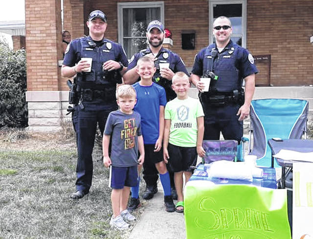 WPD patrolmen (back, L-R) Derrick Marcum, Alex Rosado and John Michael Warnecke recently stopped to play football with local children. (front, L-R) Owen Kimmey, James Bunch and Gavin Bunch had been outside selling lemonade.
