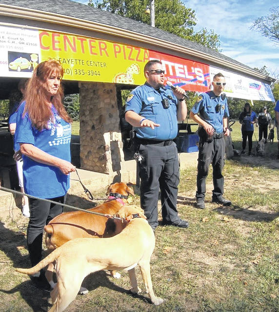 Prior to the start of the Walk Against Cruelty, Chief Humane Agent Brad Adams (M) gave a speech to the participants. The two dogs standing beside Cindy Zindorf (L) are Hank and Schatzi. Adams and Humane Agent Nick Marando (R) led the walk alongside Hank, Schatzi, Galaxy (not pictured) and Hershey (not pictured).