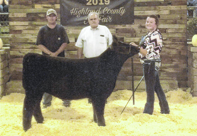 "Pictured is Natalie Lindsey with her Grand Champion Heifer ""Dolly"" at the Highland County Fair Open Class Beef Feeder Show. Also pictured are Shawn Lindsey and center judge Lyn Holly of Bowling Green. Approximately 73 heifers were exhibited, followed by 150 steer feeder calves. Lindsey's heifer was born and raised on the family farm where she resides with her parents, Shawn and Aimee, and brother, Nic Lindsey. Lindsey is a freshman at Miami Trace High School."
