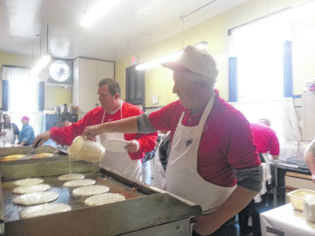 Lions Jeff Fetters and Barry Bonham, and others frying sausages for a hungry crowd at the previous the semi-annual Pancake & Sausage Supper. The next supper will be on Nov. 9.