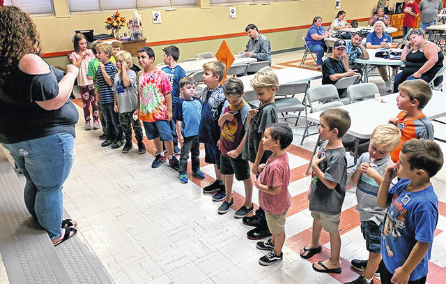 Cubmaster Sheena Huseby (left) challenges new Bobcat rank recipients during a ceremony held by Pack 112.