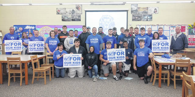 Several volunteers, including members of the Washington High School football team, joined together on Saturday morning to spread information door-to-door about the WCHCS 1 percent, seven-year income tax levy that is on the ballot for the 2019 general election.