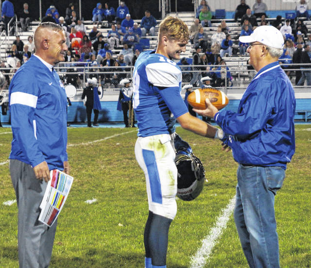 Washington Blue Lion senior Eli Lynch, center, has surpassed the all-time career receiving yards record of 1,534 yards, previously held by Preston McClendon. Lynch was recognized at halftime of the game against Chillicothe Friday, Oct. 4, 2019. Lynch's current receiving yardage total after the game is 1,602 yards. Presenting Eli with one of the game balls is former Washington High School athletic director and Eli's grandfather, Dale Lynch. Washington head coach Chuck Williamson, left, looks on.