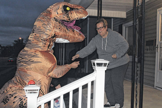 "The annual Beggars' Night was held Thursday evening despite harsh winds and low temperatures. Several residents could be seen traveling door-to-door and kids proclaiming ""Trick-Or-Treat"" could be heard throughout the evening. Randy Dean as a T-Rex receives a few sweet treats from Debbie Fitzpatrick who greeted every child at the door."