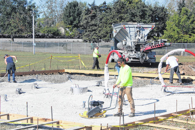 Work continued this week on a Splash Pad water attraction coming to Washington Court House. Crews poured concrete, flattened the site, and parts of the pad — such as red hoops and pipes — could be seen installed ready for the next steps.