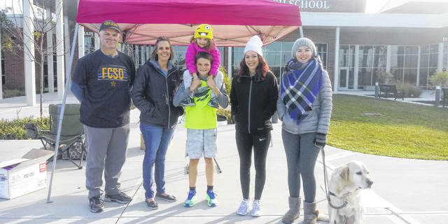 At the Fayette County Victim Witness 5K Superhero walk/run, Lucas King finished first at a fast pace he kept up throughout the track. Pictured (L-R): Miami Trace Resource Officer Monty Coe, Director of Fayette Victim Witness Stefani Payton, Lucas King, Alexis Crabtree, Ashley Gigley and PJ. The young girl on Lucas' shoulders is his sister, Lilly.