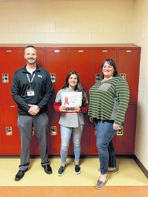 "Hallie Sword was selected as the Miami Trace Middle School winner of the Write-in Red Essay Contest for the 2019 Red Ribbon Week. She was awarded a $100 prize by Paint Valley Alcohol, Drug Addiction and Mental Health (ADAMH) Board for her winning essay, ""A Future Full of Hopes and Dreams."" Standing with Hallie is MTMS Principal Mr. Jason Binegar and her English Language Arts teacher, Mrs. Courtney Donson."