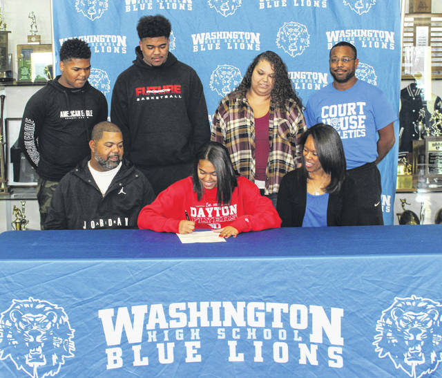 Washington High School senior Rayana Burns (seated, center) signs a letter of intent to attend the University of Dayton Friday, Nov. 15, 2019. She is flanked by her parents, Richard and Shawna and (in back, l-r); siblings Rishuan, Richie, Adrienne and Washington head track coach Louis Reid.