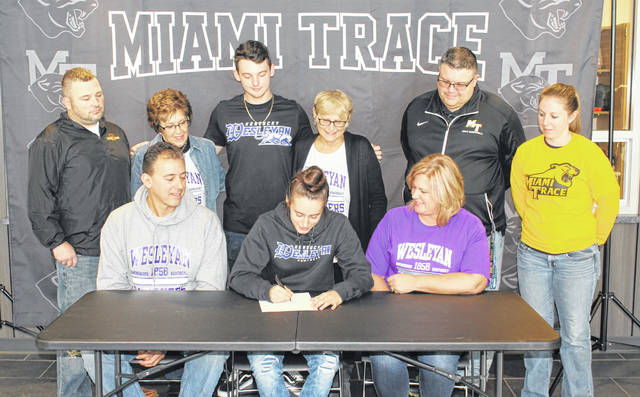 Miami Trace High School senior Shaylee McDonald (seated, center) on Friday, Nov. 16, 2019 signed a letter of intent to attend Kentucky Wesleyan University where she will continue her education and her basketball career. She was joined by family members, coaches and teammates for the occasion in the lobby outside the gymnasium. Above, McDonald is seated with her parents, Troy and Stephanie and (standing, l-r); Miami Trace head basketball coach Ben Ackley, grandmother Linda Davidson, brother Skyler, grandmother Pam Heath, and coaches Shawn Grooms and Kayla Dettwiller.