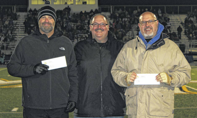During halftime of the Washington at Miami Trace football game, Friday, Nov. 1, 2019, McDonald's of Fayette County and Jamestown owner and operator, Nick Epifano, made several donations to Miami Trace and Washington schools. Above, Epifano, center, gives $500 each to David Lewis, left, Superintendent of Miami Trace Local Schools and Tom Bailey, right, Superintendent of Washington Court House City Schools.