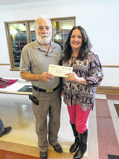 Fayette County Historical Society President Glenn Rankin (L) recently accepted a check from Beth McCane (R) of Carriage Court. McCane helped organize the historical hayride tour of Washington Cemetery. The check was for a donation to the historical society in the amount of $1,320 which came from the funds raised from the tour.