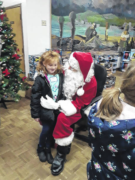 This Record-Herald file photo from the 2017 Needy Kids Christmas Party shows one of the students talking to Santa before getting a new toy. The party for 2019 will be held this Wednesday with kids from multiple elementary schools in Fayette County attending.