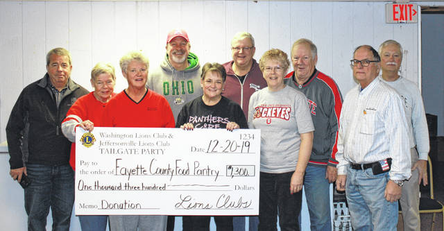 Representatives of the Fayette County Food Pantry accepted a check of $1,300 presented by the Jeffersonville and Washington Court House Lions clubs from proceeds from the Buckeye Tailgate Party. Volunteers pictured are: (L-R) Tony Anderson, Diane Rodgers, Carol Carey, Joe Black and Pantry co-director Norma Kirby along with Lions Dan Dean, Pantry co-director Sue Willis, Jay Carey, Larry Schriver and Bob Mowry.