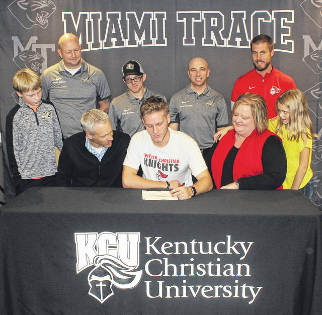 Miami Trace senior Kody Burns, seated, center, flanked by his parents and siblings, signs a letter of intent on Friday, Dec. 6, 2019 to attend Kentucky Christian University where he will continue his education and his soccer career. (front, l-r); Landon Burns, Keith Burns, Kody Burns, Lori Burns, Katlynn Burns; (back, l-r); Miami Trace assistant coaches Heath Johnson and Sean Sweeney, head coach Josh Thoroman and Kentucky Christian head coach Jeremy Miller.