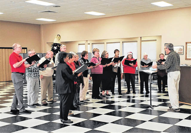 The Fayette County Retired Teachers Association's December luncheon meeting featured holiday entertainment by approximately half the members of the Fayette County Choral Society, which will be performing a joint concert of both secular and sacred music with the Fayette Community Band this coming weekend: 3 p.m. Sunday, Dec. 8, in the Historic Washington Auditorium. The singers are directed by retired MTHS vocal teacher Richard Glass; teacher David Penwell, not visible at the piano at right, is the accompanist (in addition to being a musician in the band).