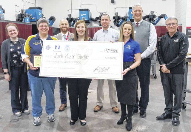 Miami Trace High School agriculture teacher Wendi Mizer Stachler (holding left side of check in FFA shirt) is pictured with representatives from Great Oaks, Nationwide, Miami Trace High School, the Wilber-Price Insurance Group, Ohio FFA and the Ohio Farm Bureau after they announced she was one of 10 finalists in the running for the 2019-20 Golden Owl/Ag Teacher of the Year on Friday at the high school.