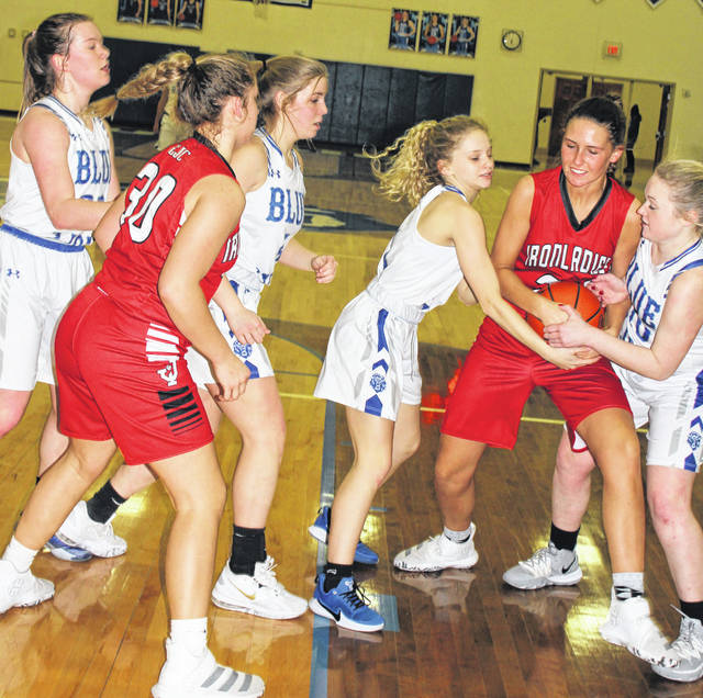 At right, Washington freshman Allie Mongold (left) and senior Abby Tackage force a held ball situation during a Frontier Athletic Conference game against Jackson Wednesday, Jan. 29, 2020. Also pictured for Washington are senior Halli Wall, left and freshman Kendall Dye.