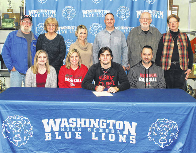 Washington High School senior Ryan Schwartz, seated, third from left, with his family after signing a letter of intent to attend Muskingum University. The ceremony was held in the lobby of the high school gymnasium Tuesday, Jan. 21, 2020. (front, l-r); sister Erin Schwartz, mother Trina Schwartz, Ryan Schwartz, father and Washington Blue Lion head baseball coach Mark Schwartz; (back, l-r); grandparents Brian Finney and Debbie Finney, aunt and uncle Melinda Schwartz and Eric Schwartz and grandparents Dick Schwartz and Sue Schwartz.
