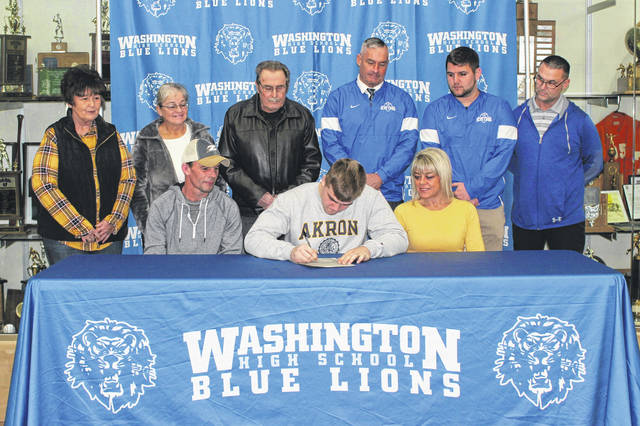 Washington High School senior Collier Brown, seated, middle, signs a letter of intent to attend the University of Akron where he will continue his education and his football career as a member of the Zips football team. Seated with Brown are his parents, Blanton and Christy Brown and, in back (l-r); grandmother Sue Brown, grandmother Phyllis Havens, grandfather Rudy LeBeau, Blue Lion head coach Chuck Williamson and coaches Tyler Flora and Eric Downey. The ceremony was held on National Signing Day Wednesday, Feb. 5, 2020 in the lobby outside the gymnasium at Washington High School.