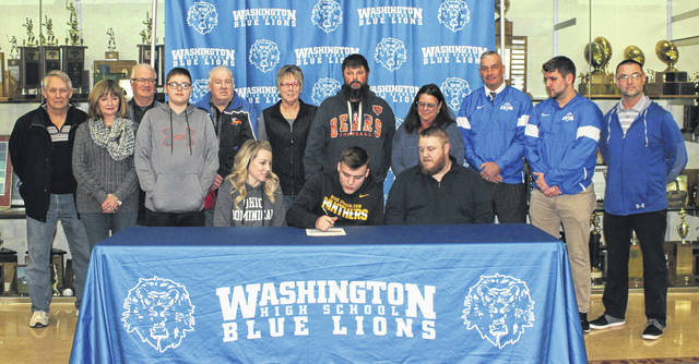 Washington High School senior Garitt Leisure, seated, middle, signs a letter of intent to attend Ohio Dominican University where he will continue his education and his athletic career as a member of the Panthers' football team. He was joined on National Signing Day, Wednesday, Feb. 5, 2020 by his parents, (flanking him) Ashlee Hyer and Duke Leisure; (standing, l-r); grandfather Jay Hyer, grandmother Peggy Hyer, grandfather Kenny Thacker, brother Kobie Hyer, grandfather Russ Richards, grandmother Debi Richards, step dad Aaron Hyer, grandmother Sonia Thacker, head coach Chuck Williamson and coaches Tyler Flora and Eric Downey.