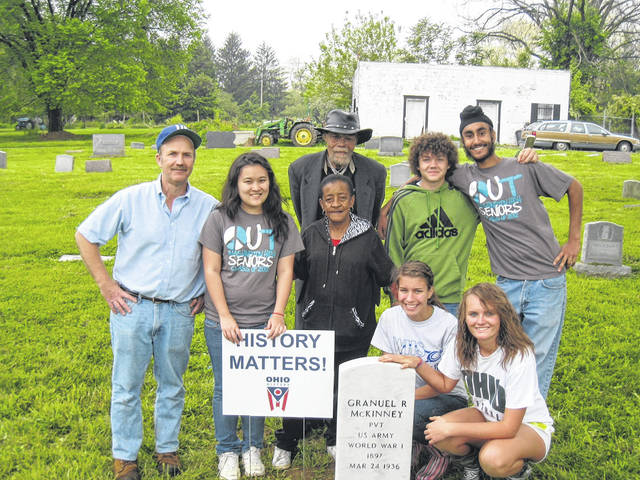 In this courtesy photo, students from Washington Court House met with community leaders at an African American Cemetery with a World War I soldier's headstone. These students were a part of LaRue's research history class when he taught at Washington High School and were active in restoring head stones for veterans.