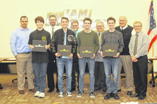 The Miami Trace Board of Education honored four young men during its Monday meeting for their success in the National Merit Scholarship Program. The four (front row, left to right) — John Bryant, Caleb Perry, Henry DeBruin and Simon DeBruin — were presented with a certificate and congratulated by the board for their academic success. All four were named commended students last September after being selected as part of 50,000 top scoring students. The DeBruins have since continued to be named finalists this month and will go on to potentially win thousands of dollars in scholarships from the National Merit Scholarship Corporation.