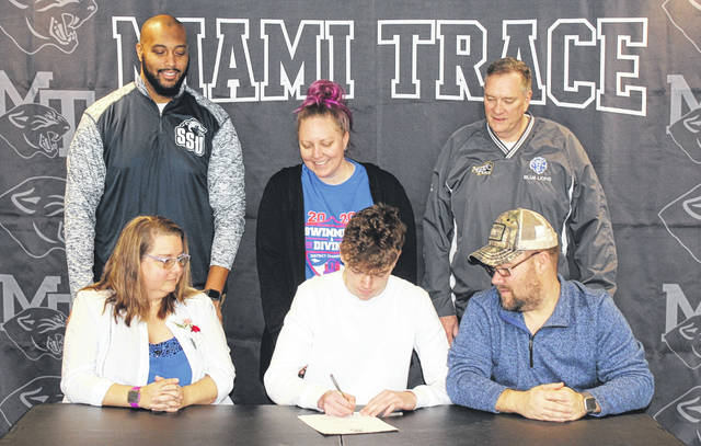 Miami Trace senior Jacob Downing, seated, center, on Feb. 14, 2020 signs a letter of intent to attend Shawnee State University where he will be a member of the Bears swim team and continue his education. He is flanked by his parents, Tracy and John and joined by (standing, l-r); Shawnee State University swim coach Gerald Cadogan, Miami Trace swim coach Katie Kasberg and assistant coach Keith Foster.
