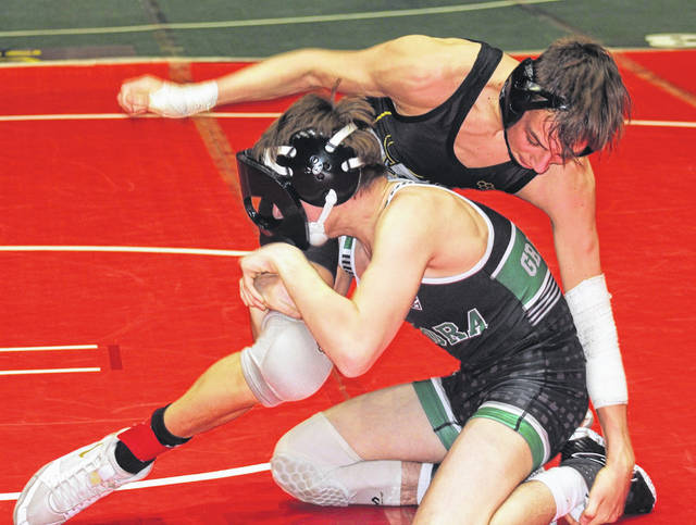 Miami Trace sophomore Weston Melvin reaches down to grab the ankle of Aurora junior Robbie Sagaris during a 113-pound match at the State dual team tournament Sunday, Feb. 16, 2020 at St. John Arena on the campus of The Ohio State University.