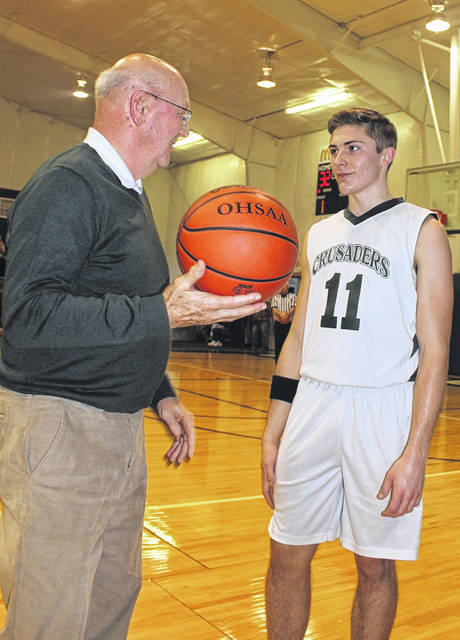 Fayette Christian School boys basketball coach Gary Shaffer presents Crusaders senior Nicholas Epifano with the ball after Epifano reached the 1,000-point scoring mark for his career in a victory over the Adams County Eagles Saturday, Feb. 8, 2020 at FCS.