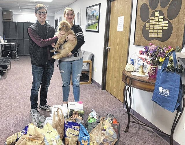 "Miami Trace High School freshman class officers recently worked to provide much needed supplies to the Fayette Regional Humane Society. Pictured are class president Jacob Cline, class vice president Sara Dawson and ""Willow,"" a puppy at the Humane Society."