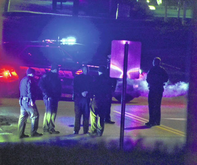 Law enforcement personnel are pictured Saturday night at the scene of a fatal crash on North High Street in Hillsboro.