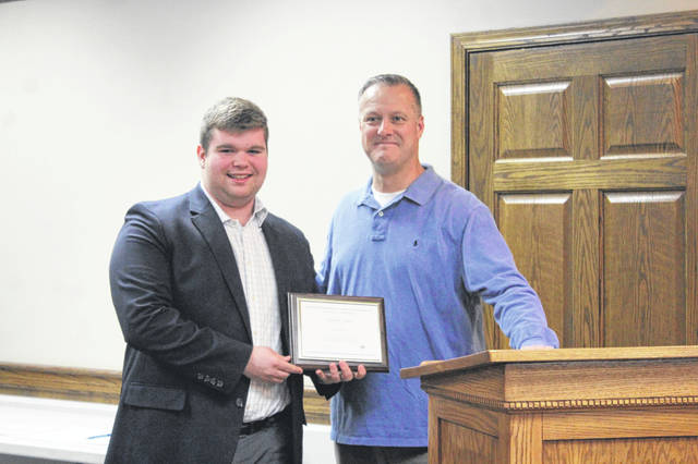 The Washington Court House City Schools Board of Education honored Trevor Minyo on Monday for being named a National Merit Scholarship finalist. Minyo is pictured with board member Craig Copas.