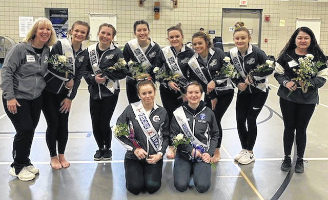 The Miami Trace gymnastics team (with members from Greeneview and Washington High Schools) poses prior to processional of gymnasts at the District meet Feb. 22, 2020. (front, l-r); Lizzy Valentine (Greeneview) Abby Rose (Washington); (back, l-r); head coach Susan Holloway, McKinley Kelley, Averey Cockerill, Grace Rolfe, Kandice Mathews, Milana Maceoce, Devan Thomas and assistant coach Chasity Thomas.