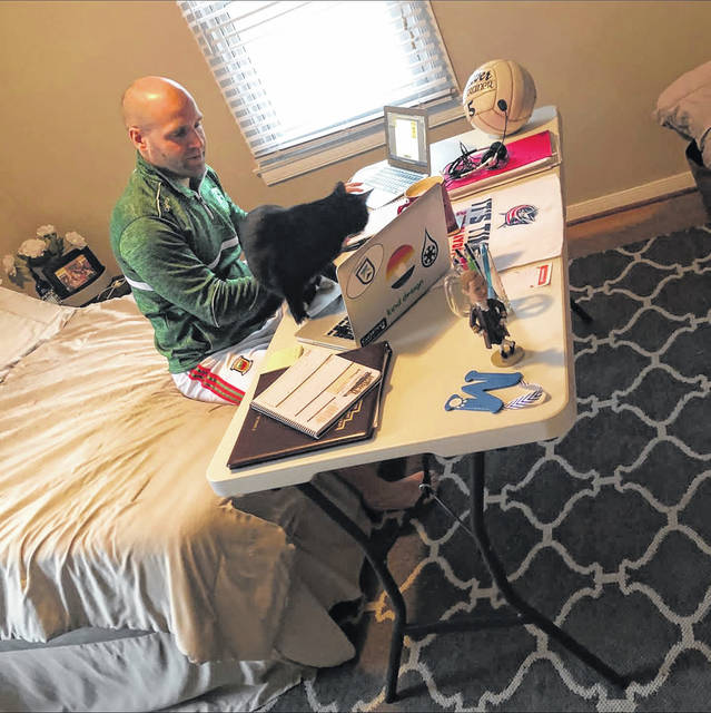 Local school districts this week continued to educate and assist children forced to stay away from school due to COVID-19 with various programs such as Distance Learning and the Big Blue Bus program. Pictured is Washington Court House City Schools' eighth grade social studies teacher, Chris McAndrew, working from home to ensure his students continue to learn during this difficult time.
