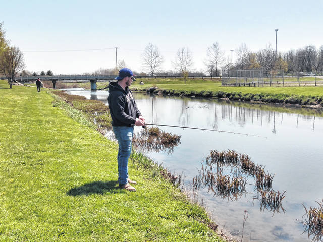 With the nice weather on Wednesday, two locals were found fishing along Paint Creek at Christman Park. Pictured are Elijah Krech (close) and Jay Riley (in the distance).