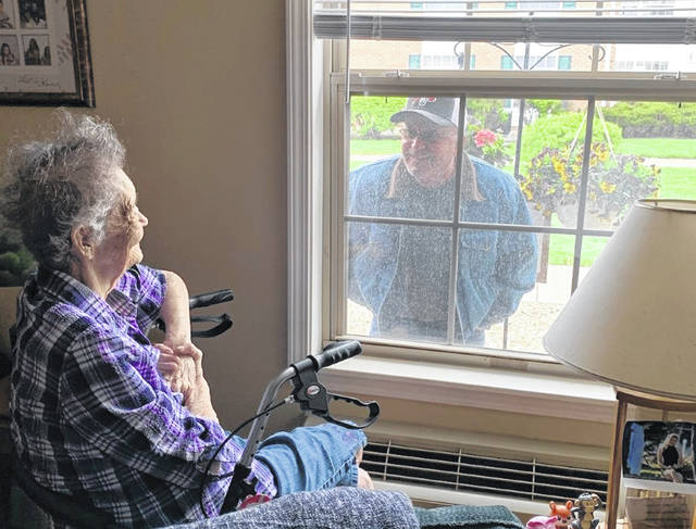 "Family and friends of residents of Carriage Court of Washington are taking part in ""window visitations,"" which have been occurring at all local facilities. Pictured are Betty Crocker and her son, Ray Crocker."