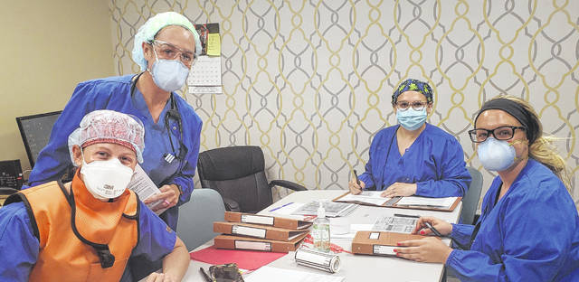 From left to right, members of the FCMH Surgery Center team, Tara Mossbarger, Anne Roberts, Lindsey Gustin and Kristin Landrum prepare for a day of procedures, now allowed by the Ohio Department of Health and Governor DeWine.