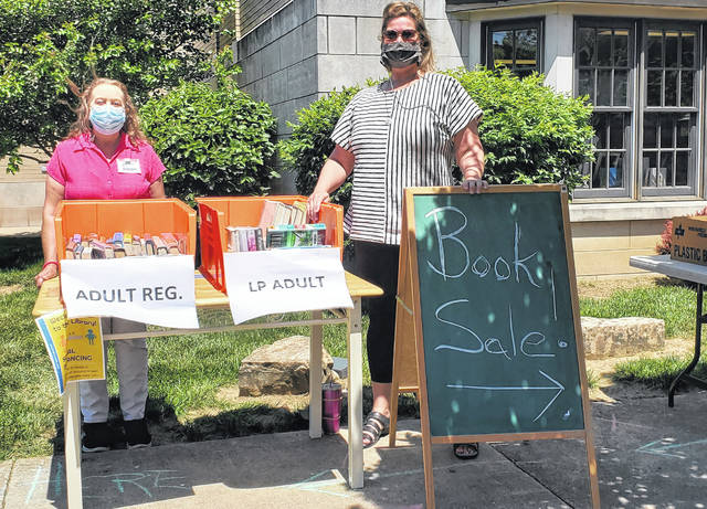 Carnegie Public Library held an outdoor book sale on Monday and Tuesday while the weather was nice. Pictured are Branch Manager Susan Davis(left) and Library Director Sarah Nichols (right).